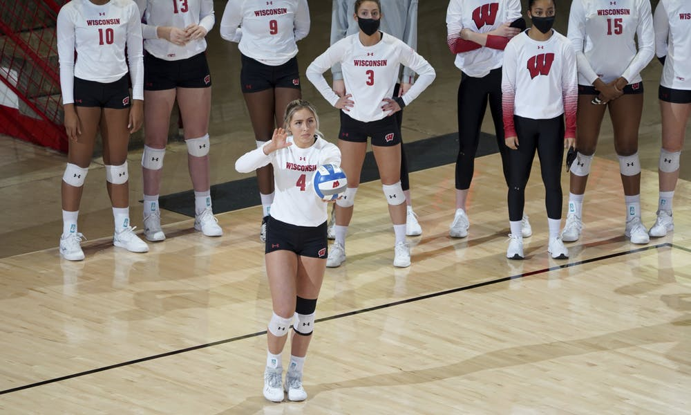 A Badger volleyball player getting ready to serve the ball.