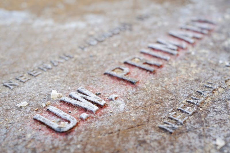 "The salt-crusted letters spelling ""U.W. Primary"" on a forged-metal manhole utility cover are pictured near the Extension Building at the University of Wisconsin-Madison during a winter day. Photo courtesy of Jeff Miller/UW-Madison."