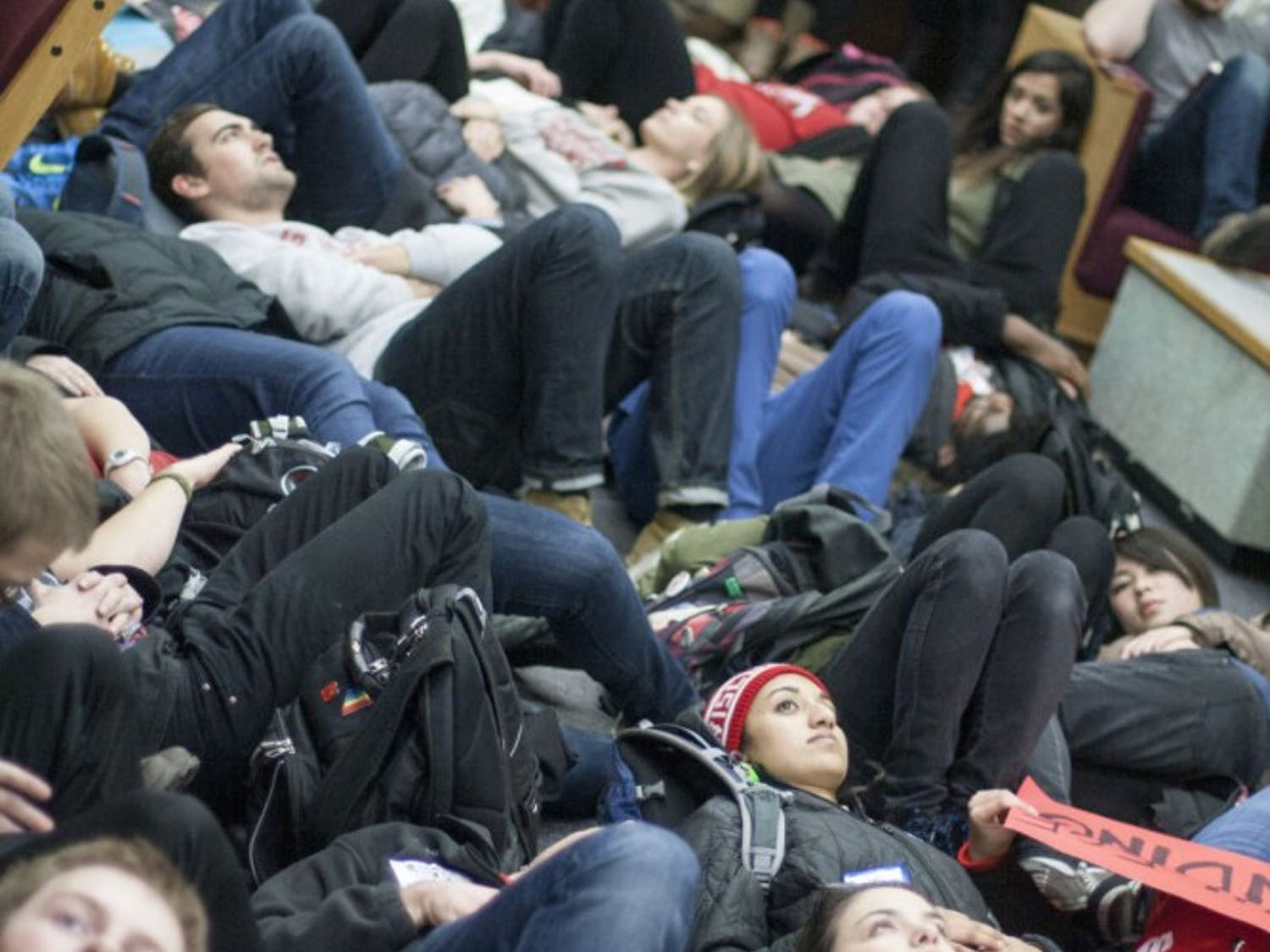 Protesters lay on the ground around students studying for finals for 20 minutes before concluding the demonstration outside the doors of the library.