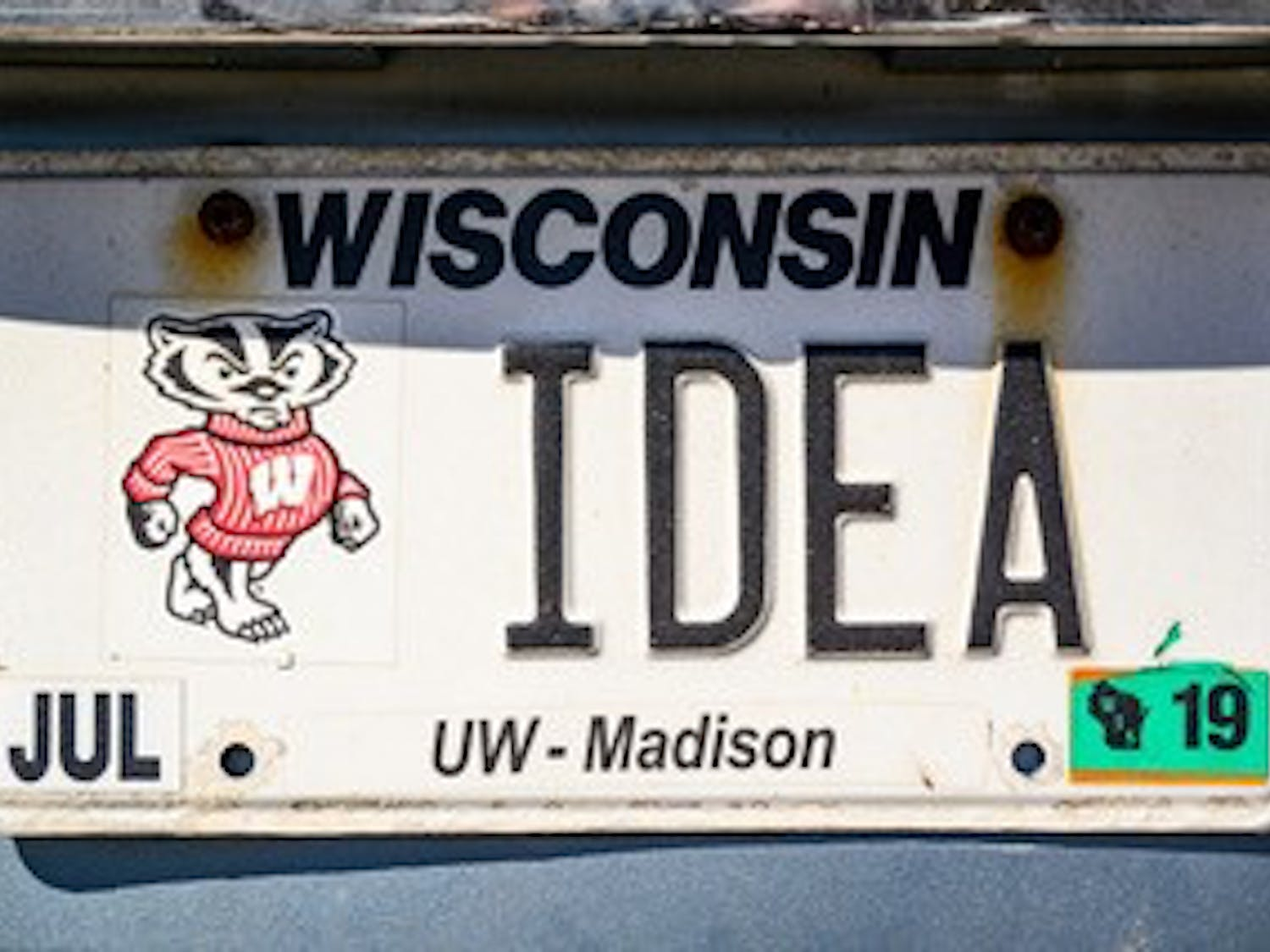 A personalized license plate displaying a nod to the Wisconsin Idea, a philosophy embraced by the University of Wisconsin System, is  spotted on a vehicle in Lot 34 on April 23, 2019. (Photo by Bryce Richter /UW-Madison)