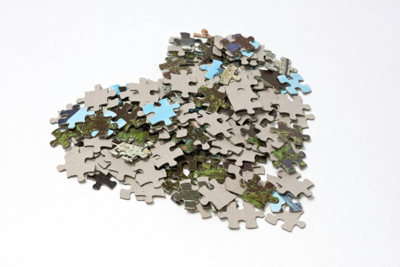 A pile with lots of small jigsaw puzzle pieces having a gray back and a front picture made of cyan and green colors. They are arranged in the shape of a heart, on a white background.