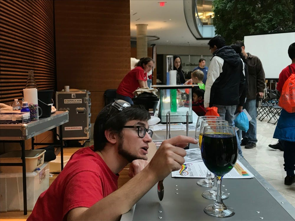 A volunteer explains the differences in pitch that occur in glasses with different amounts of liquid in them. Photo by Tyler Fox.
