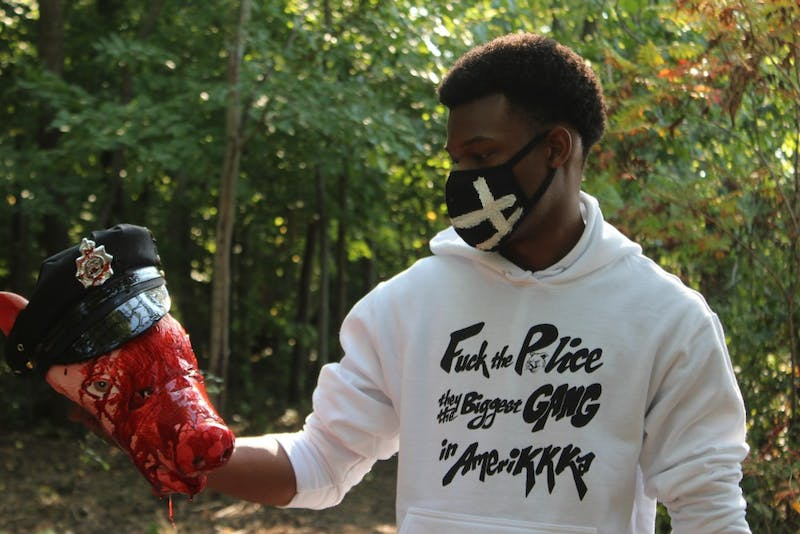 Eneale Pickett holds a beheaded police officer while promoting his new clothing line that focuses on police brutality in America.