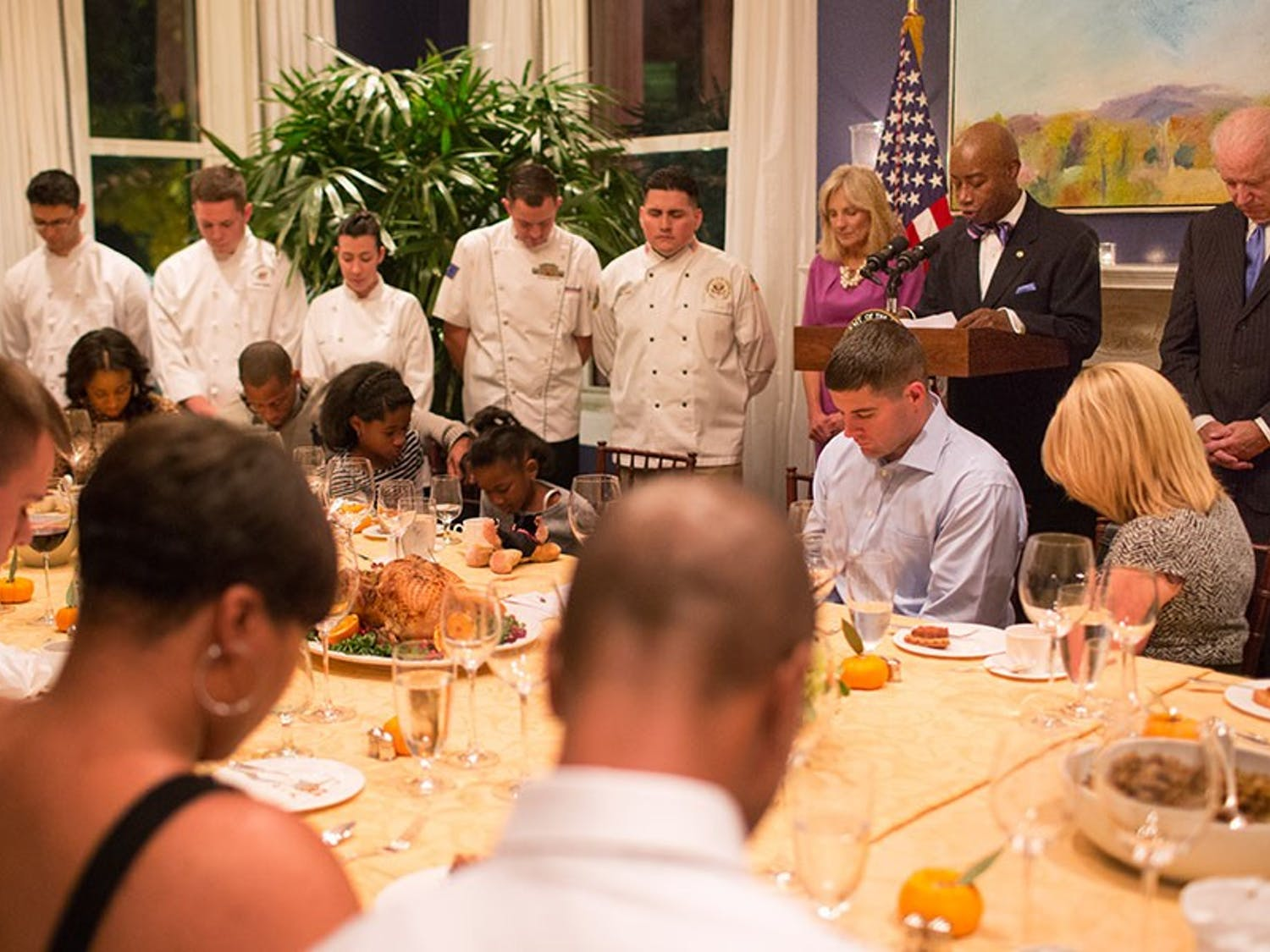 Vice President Joe Biden and Dr. Jill Biden bow their heads as Chaplain Barry Black gives the benediction during the fifth annual wounded warrior Thanksgiving dinner, at the Naval Observatory Residence, November 21, 2013. (Official White House Photo by David Lienemann)