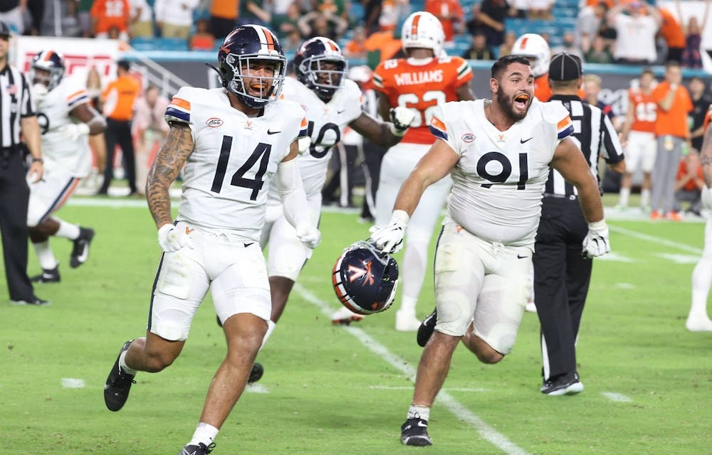 <p>Virginia junior defensive back Antonio Clary and senior defensive end Mandy Alonso celebrate after beating Miami Thursday night.</p>