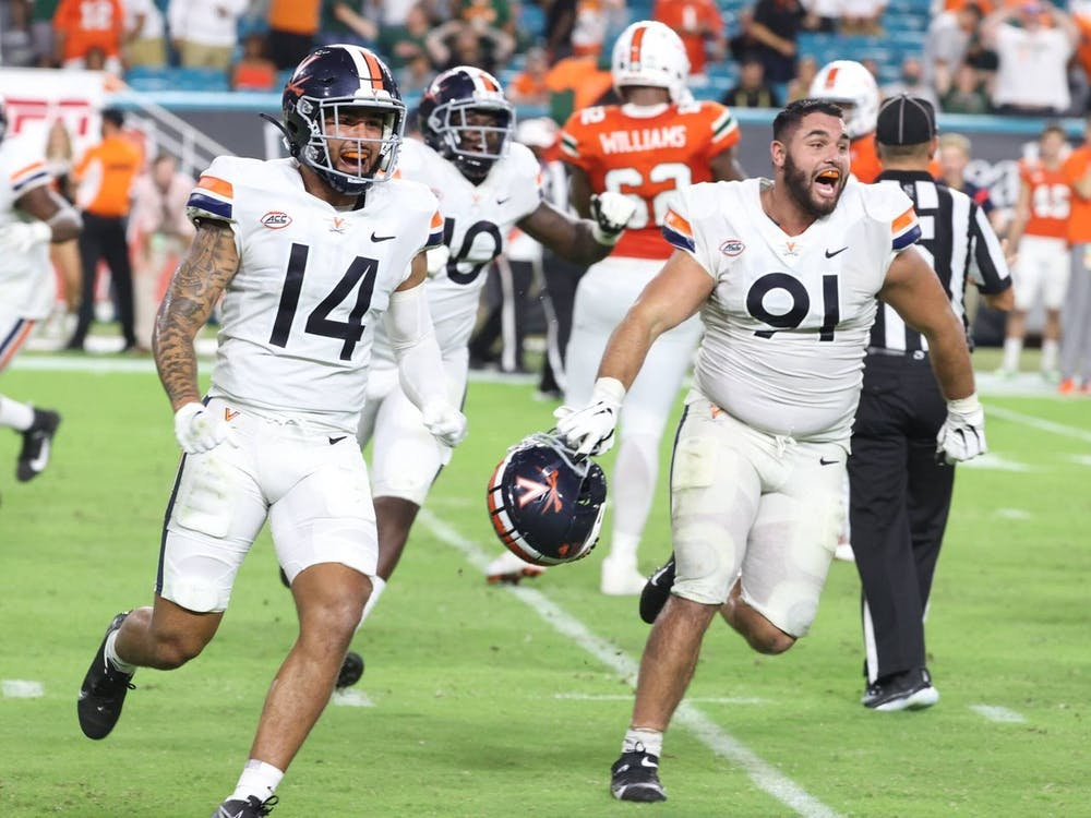 Virginia junior defensive back Antonio Clary and senior defensive end Mandy Alonso celebrate after beating Miami Thursday night.