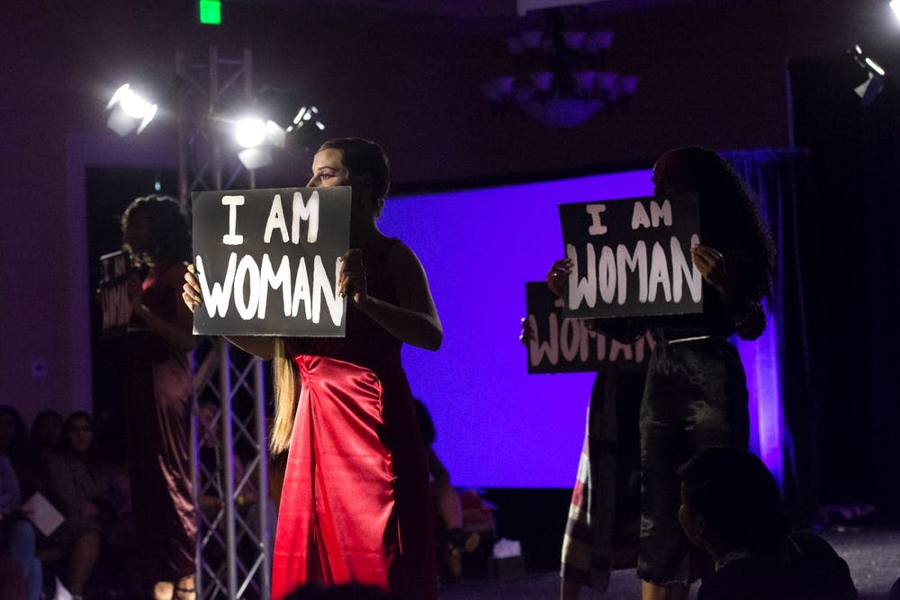 """<p>Models held signs reading """"I Am Woman"""" during all-female collection on display at this year's Fashion for a Cause show.</p>"""