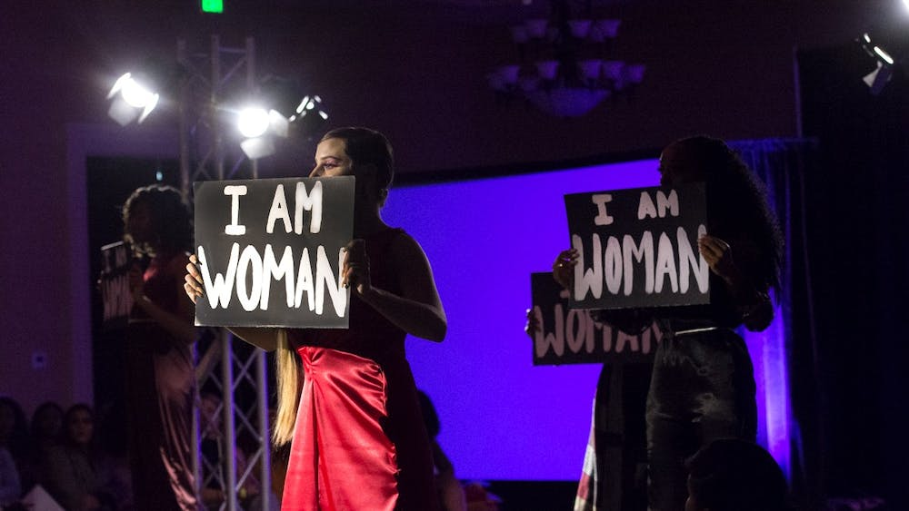 """Models held signs reading """"I Am Woman"""" during all-female collection on display at this year's Fashion for a Cause show."""