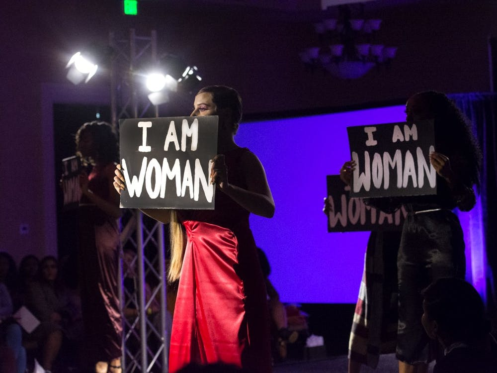 "Models held signs reading ""I Am Woman"" during all-female collection on display at this year's Fashion for a Cause show."