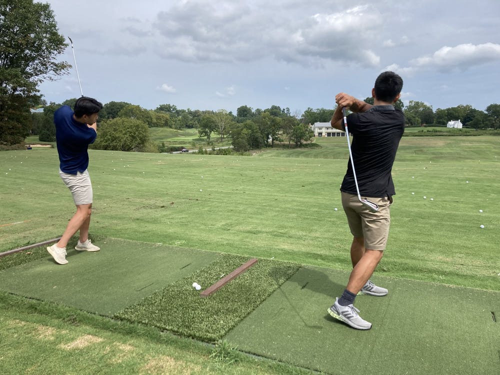 Fourth-year Engineering student Tae Chang and fourth-year College student Eric Su practice their swings on the driving range during Golf class.