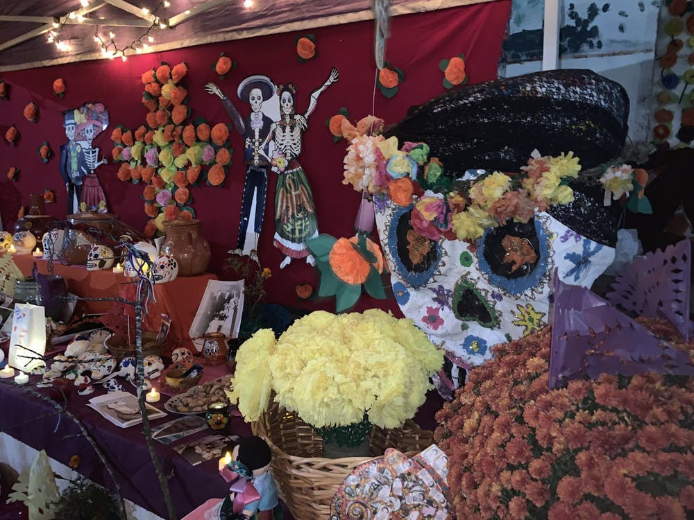 One of the multiple altars at the festival, adorned with flowers and paper marigolds. The vibrant colors of the skulls represent those who have passed.