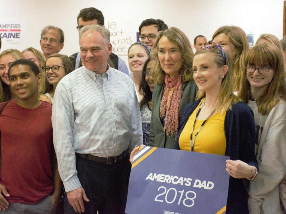 Sen. Tim Kaine and Leslie Cockburn pose for a picture with members of the University Democrats.