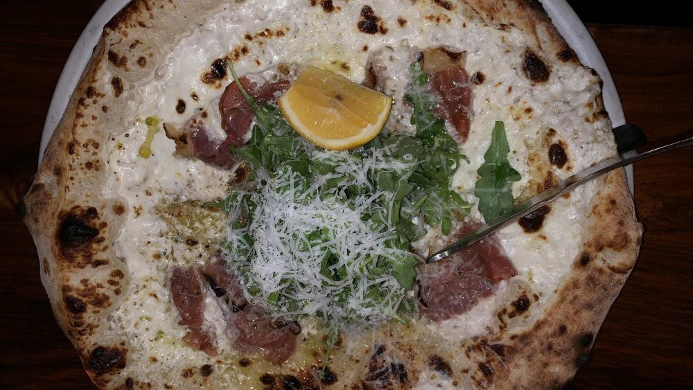 The prosciutto pizza at Lampo is topped with prosciutto, arugula, grana padano cheese and lemon.