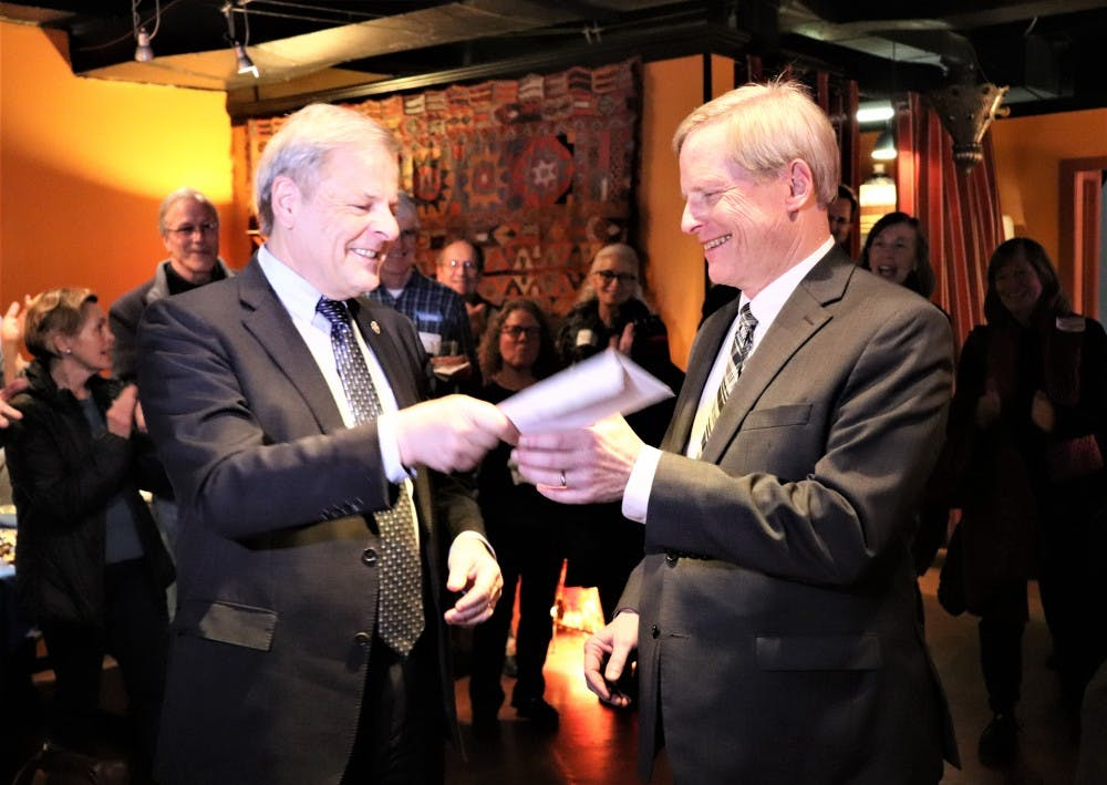 <p>Local criminal defense attorney Lloyd Snook (right) receives a check from Del. David Toscano (D-Charlottesville) during Snook's City Council campaign launch at Bashir's Taverna Tuesday.&nbsp;</p>