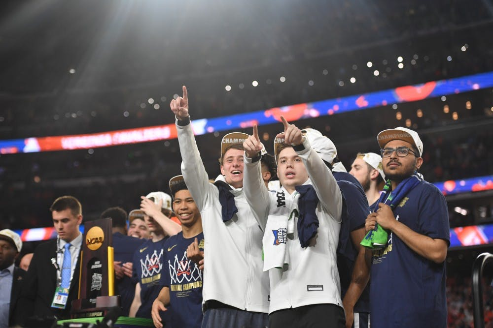 <p>Senior student managers Grant Kersey, Justin Maxey and Faris Wasim celebrate Virginia's first National Championship in program history in Minneapolis.</p>
