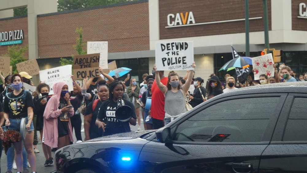 Led by a group of local black women, hundreds of community members gathered in the John Paul Jones Arena parking lot Saturday evening as part of the Defund the Police Block Party and Noise Demonstration. (CD Photo // Sophie Roehse)