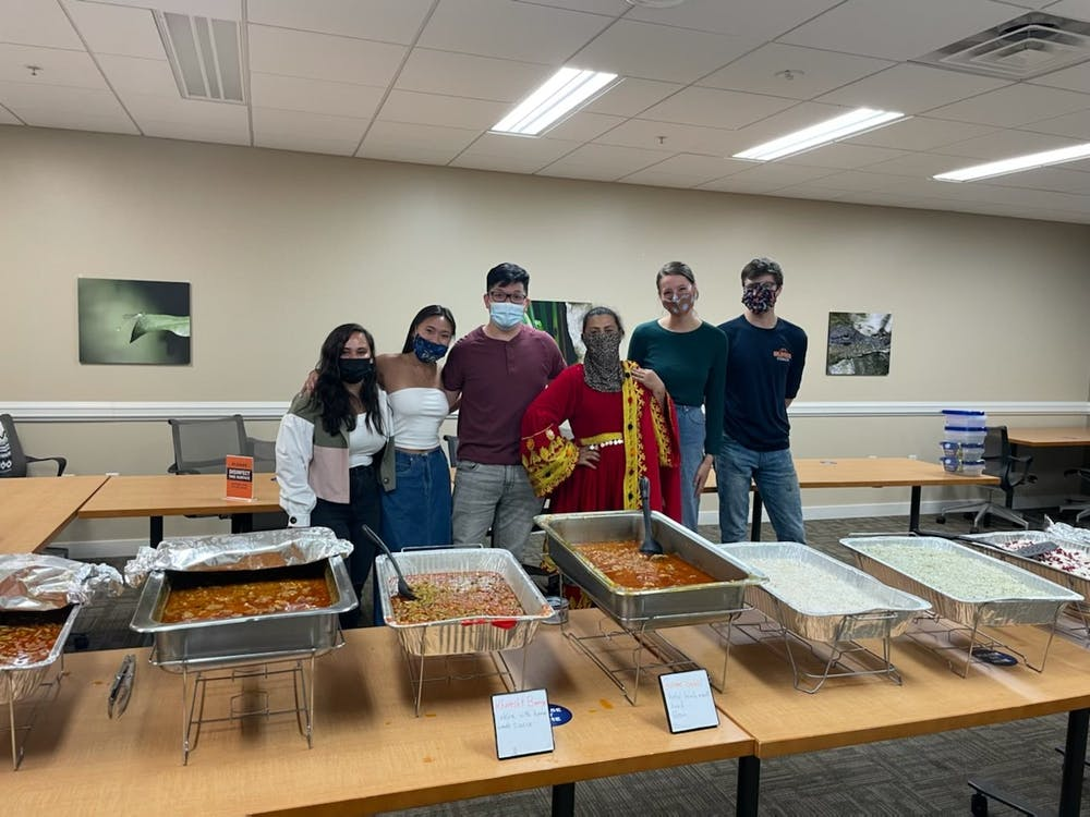 <p>Taste of Home members stand with Chef Khadija behind an array of delicious Afghan cuisine.</p>