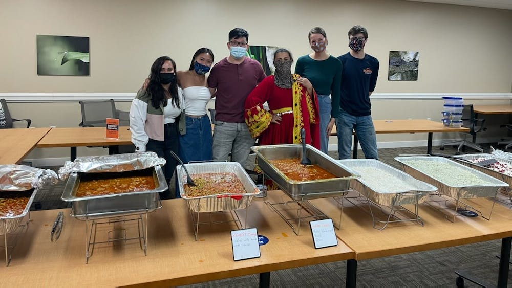Taste of Home members stand with Chef Khadija behind an array of delicious Afghan cuisine.