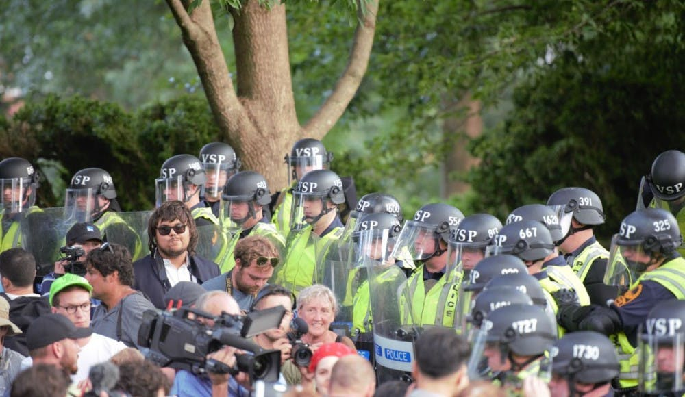 <p>Virginia State Police officers form a line between demonstrators and the adjacent Academical Village during a rally organized by U.Va. Students United near Brooks Hall Saturday Aug. 11, 2018.&nbsp;</p>