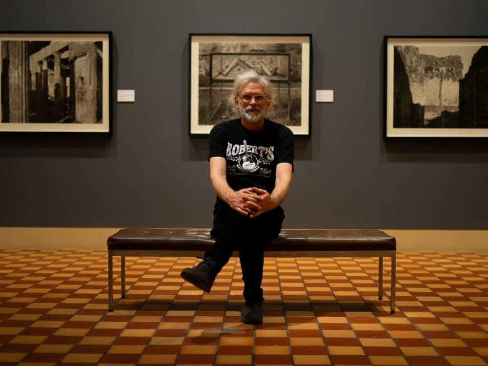 Professor William Wylie sits in front of his photo exhibit, currently on display at the Fralin Museum of Art.