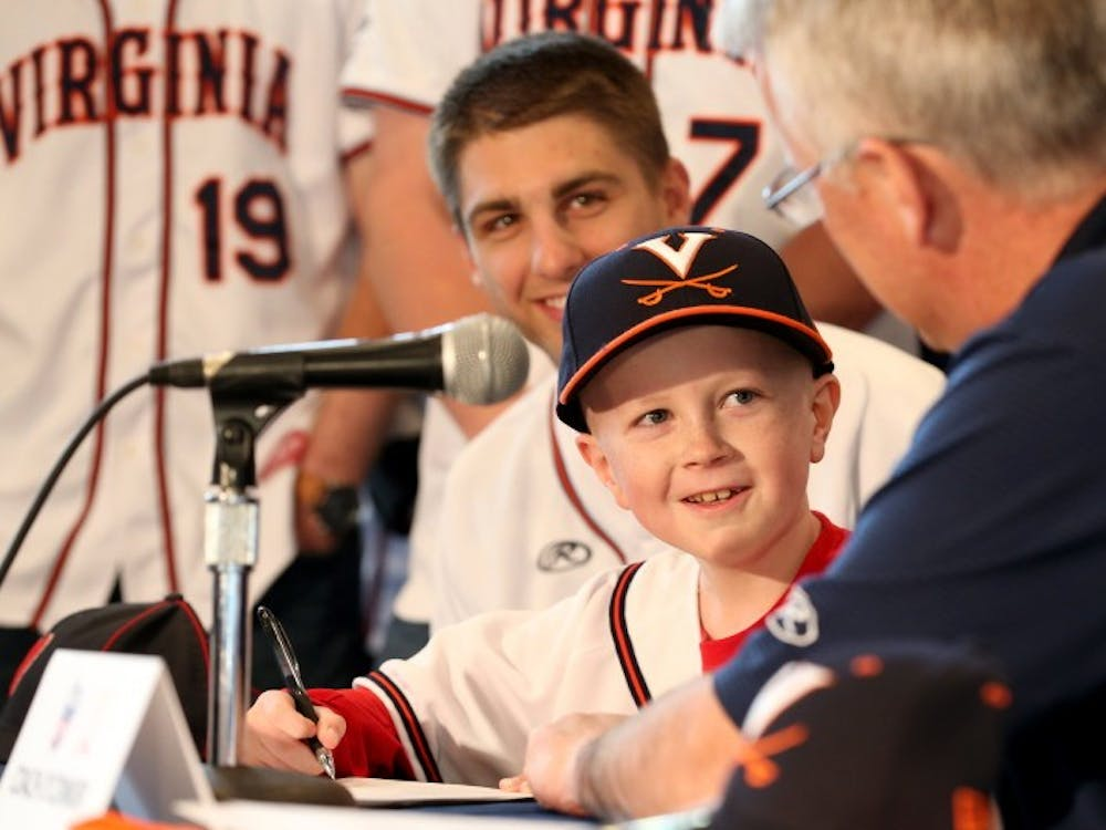 """John """"Parker"""" Staples signed a draft day letter during a press conference while surrounded by the entire Virginia baseball squad April 16."""