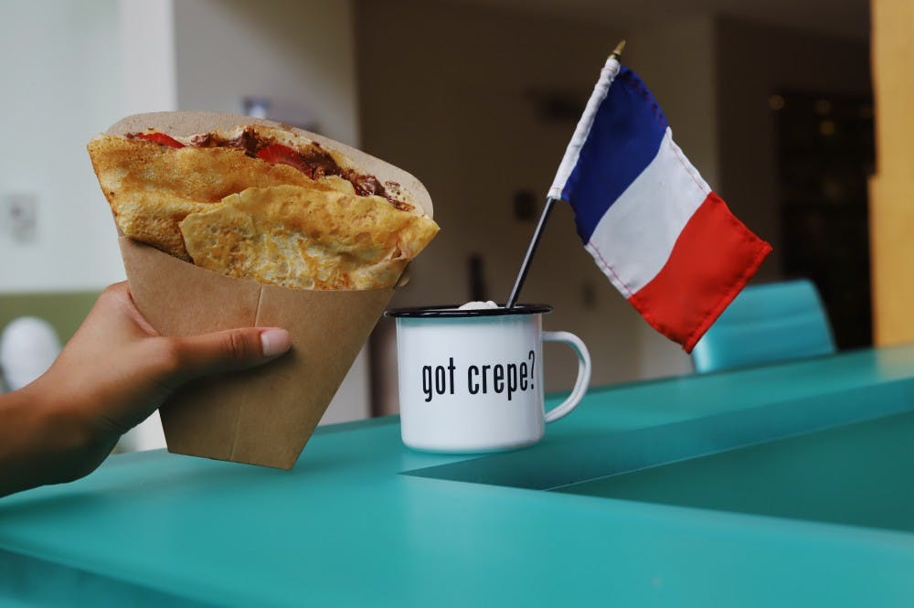 <p>De Clippeleir holds her Nutella Strawberry crepe at the Crêpe Society's location in the iLab at Darden.</p>