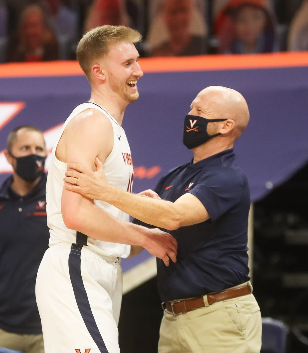 <p>Virginia senior forward Sam Hauser celebrates with assistant coach Brad Soderberg after coming off the court late in the game.</p>