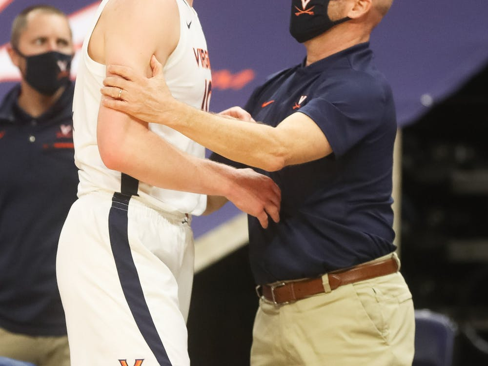 Virginia senior forward Sam Hauser celebrates with assistant coach Brad Soderberg after coming off the court late in the game.