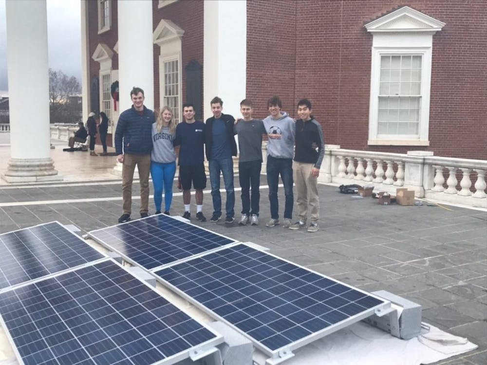 Erik Toor, leader of the Lighting of the Lawn solar energy initiative, stands with his team from Charlottesville Solar Project next to their solar panels on the Rotunda