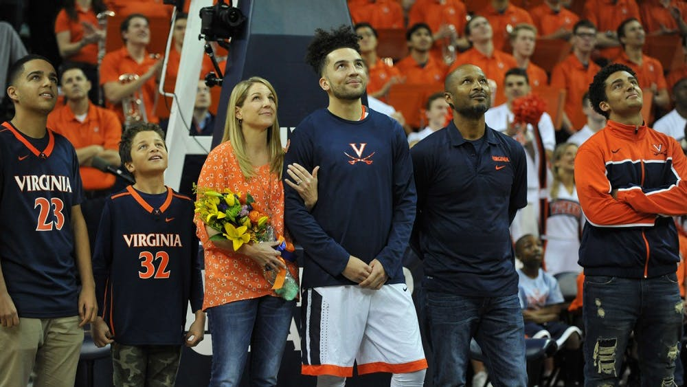 Senior point guard London Perrantes stands with his family during Virginia basketball's Senior Day.