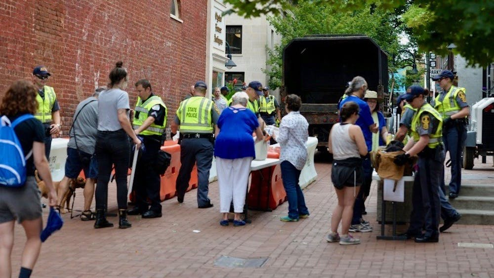 Law enforcement personnel search peoples' bags at a security access checkpoint established at Third Street on the south side of the Downtown Mall.