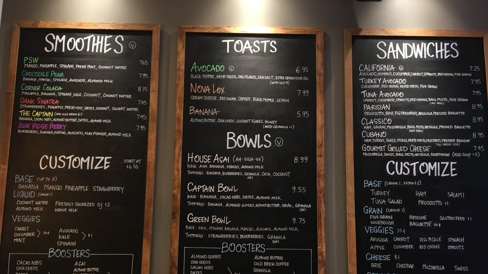Corner Juice's lists its offerings in bright chalk. Its offerings include smoothies, toasts, bowls and sandwiches.