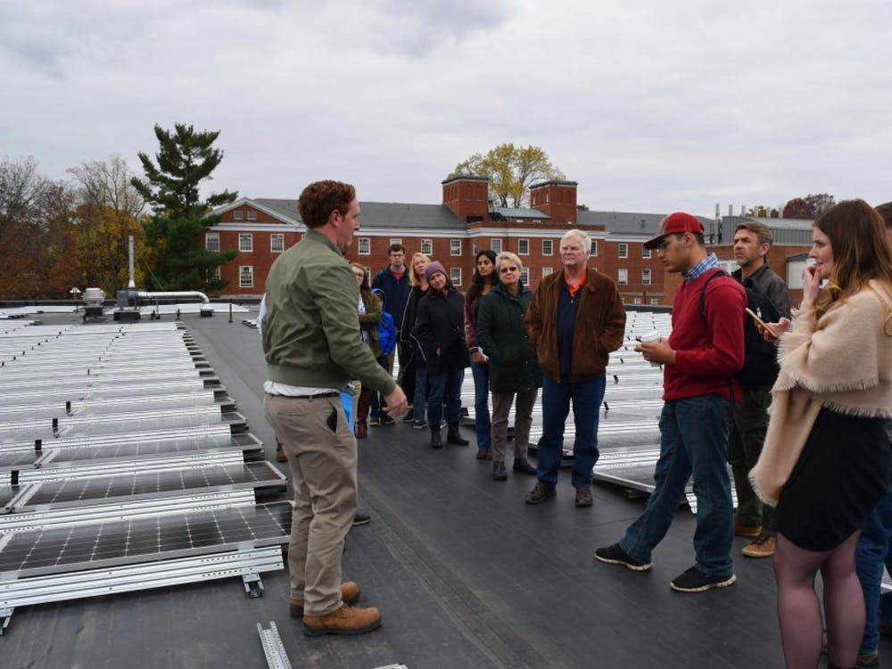 A tour looks at solar panels installed on the roof of Ruffner Hall.