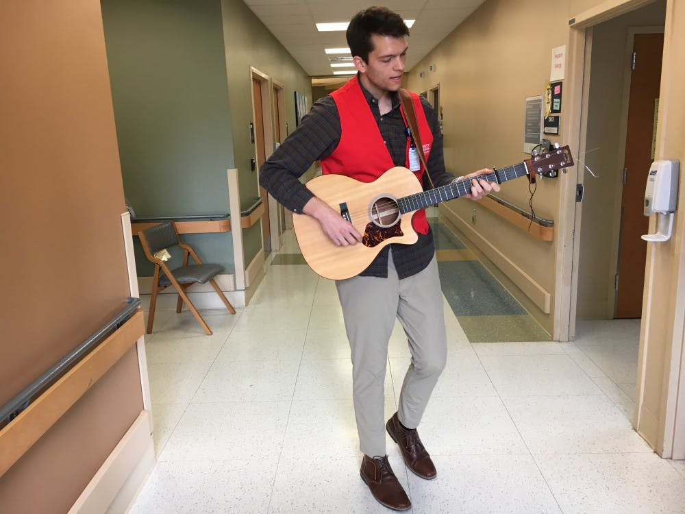 Grant Frazier, the founder of Harmonies for Healing, performing in the hallway of the Transitional Care Hospital.