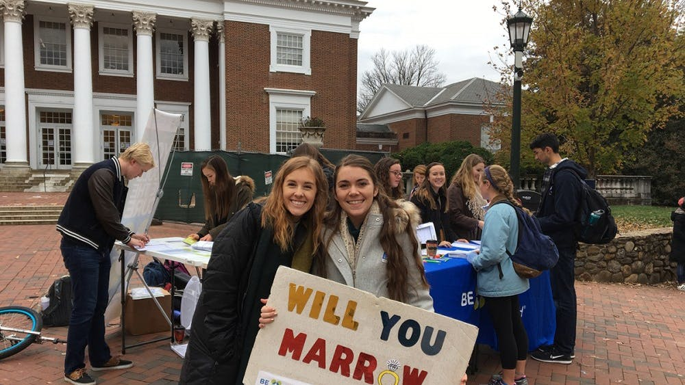 Two students hold up a sign for the bone marrow registry drive.