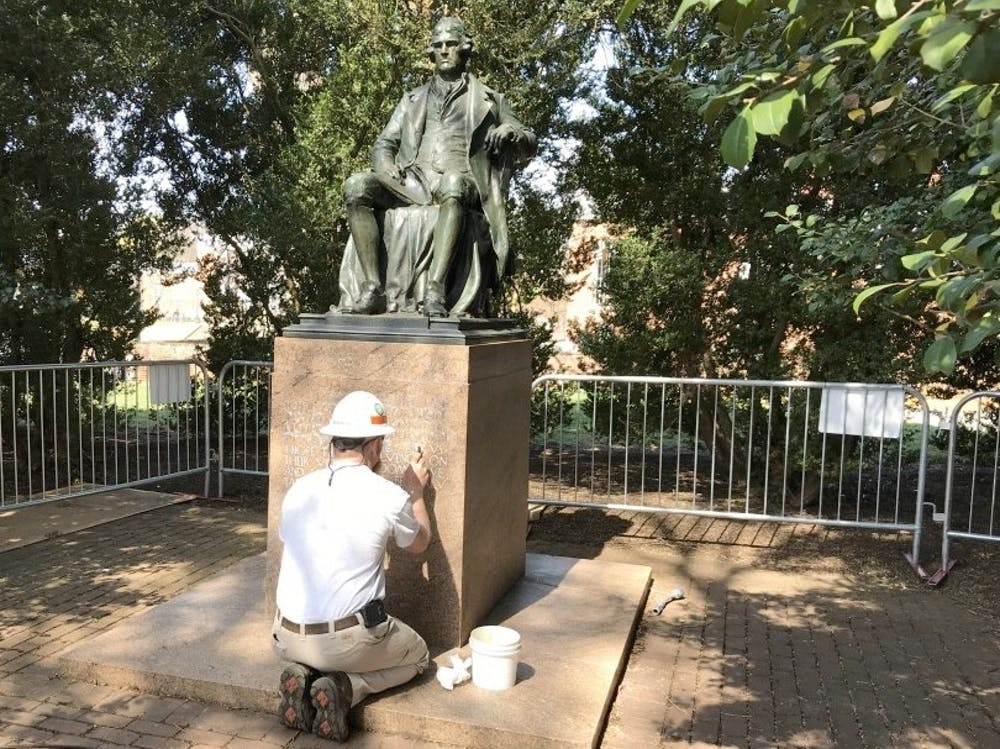 <p>A worker from &nbsp;facilities management &nbsp;works to remove paint from the base of the statue.</p>