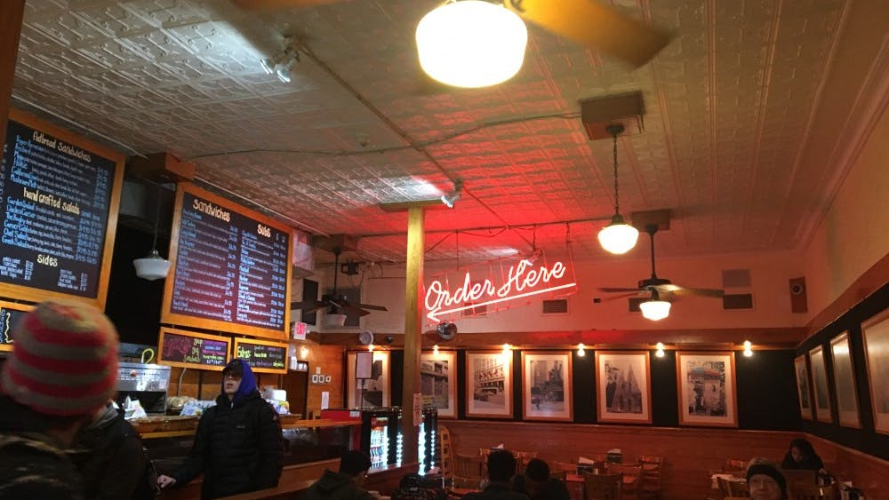 The atmosphere inside is busy and warm, very much like a real New York deli.