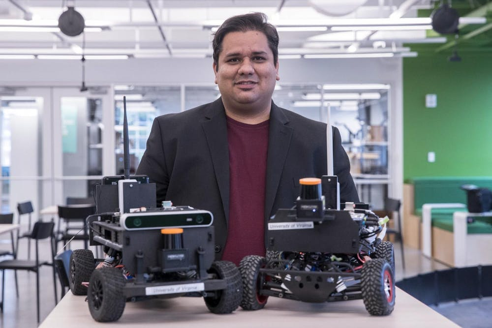 <p>Madhur Behl — assistant professor of computer science, engineering systems and environment — stands behind two model F1/10 cars.</p>