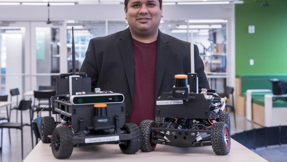 Madhur Behl — assistant professor of computer science, engineering systems and environment — stands behind two model F1/10 cars.