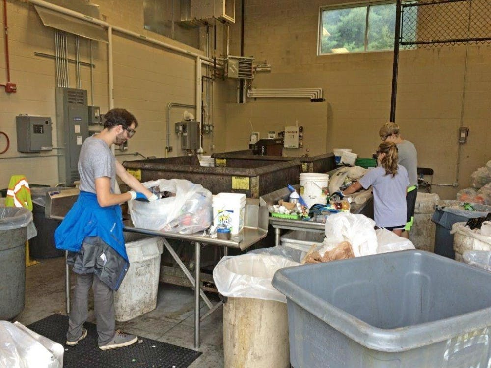 Steering away from single-stream recycling, workers in facilities management sort through bags of recycled material to further separate them to ensure cleanliness and little contamination.