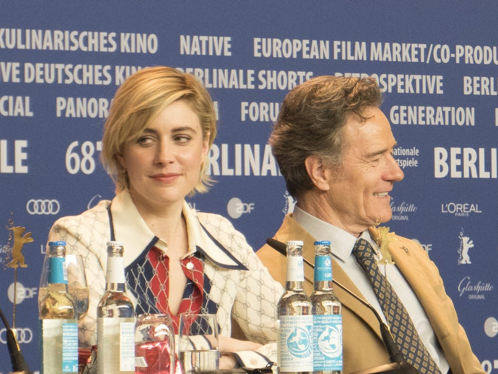 "Director Greta Gerwig in 2018 at a press event for the Wes Anderson film ""Isle of Dogs,"" alongside actor Bryan Cranston."