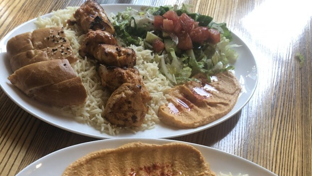 The Chicken Shish Kebab Platter consists of skewered pieces of grilled chicken breast, served with rice, salad, hummus and homemade pita bread.