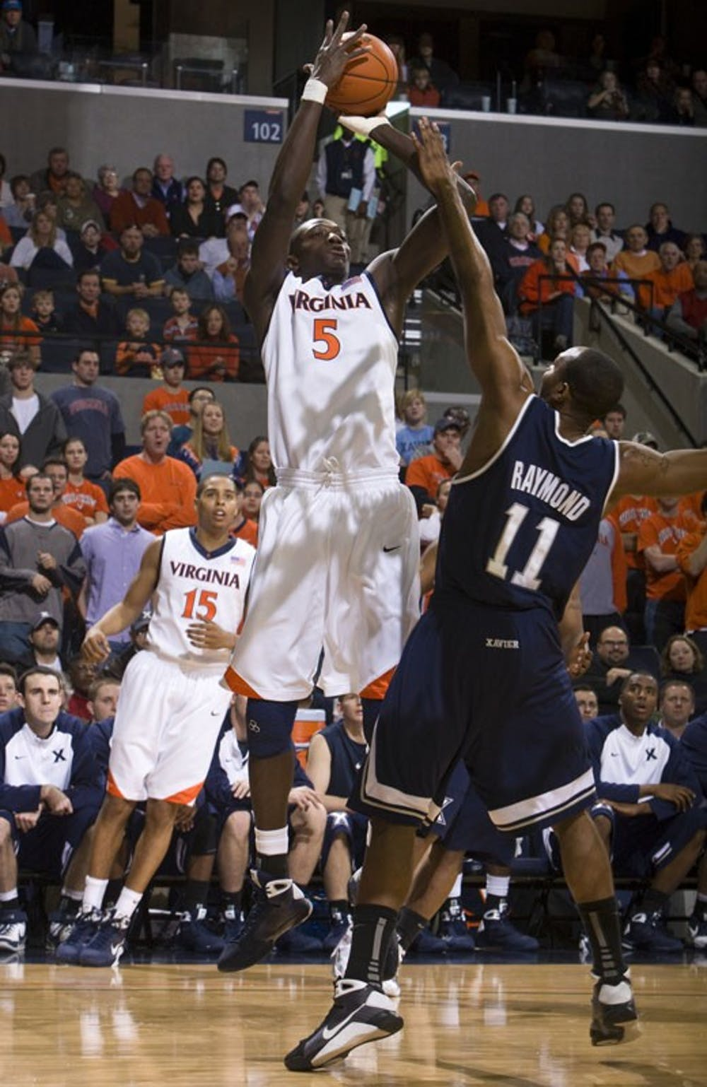 Virginia center Assane Sene (5) shoots a fadeaway jump shot over Xavier guard/forward B.J. Raymond (11).  The #22 ranked Xavier Musketeers defeated the Virginia Cavaliers 84-70 at the John Paul Jones Arena on the Grounds of the University of Virginia in Charlottesville, VA on January 3, 2009.