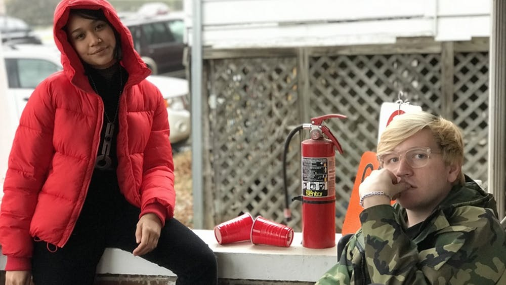 Fourth-year College student Lona Manik wears a red puffer coat from American Eagle Outfitters and third-year College student Ian Ware wears a taupe faux-fur coat from Urban Outfitters.