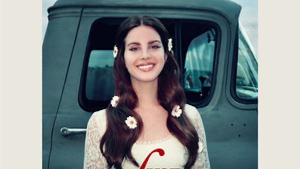 """Look no further than the album cover for an appropriate metaphor — as with all her previous releases, the cover of """"Lust for Life"""" features Del Rey posing in front of a car. Only this time, she actually smiles."""