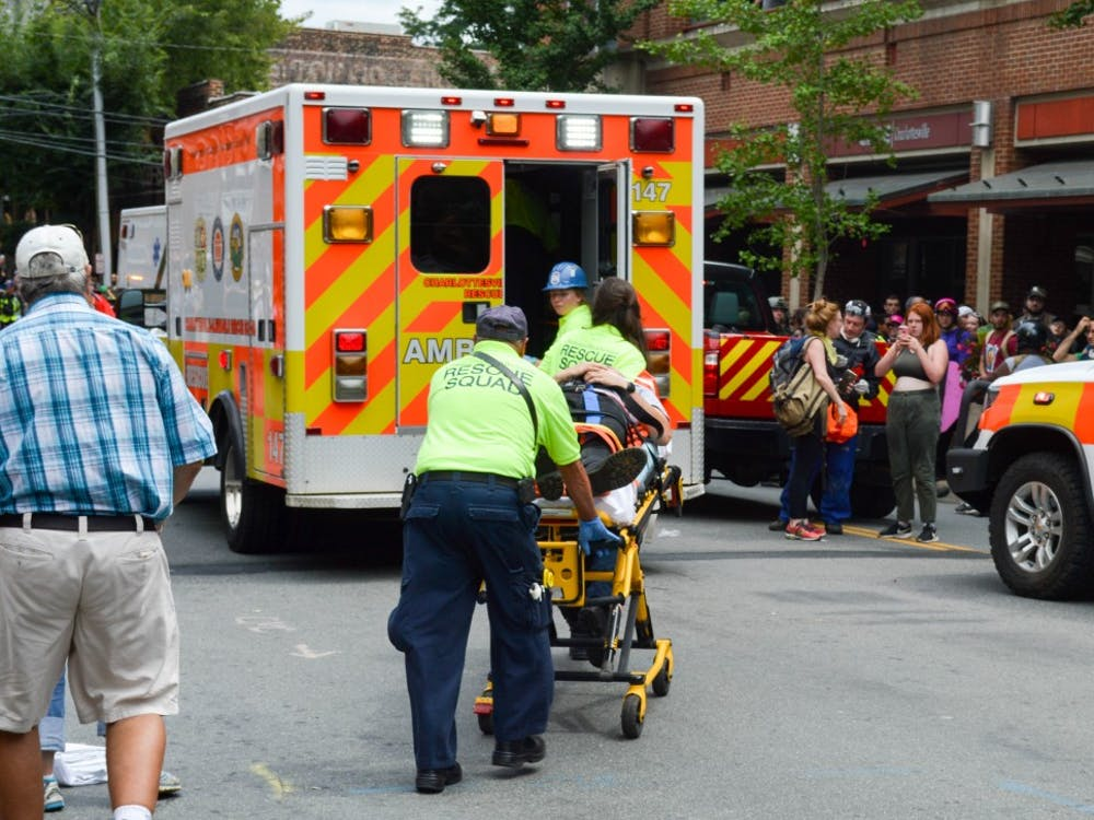 Medical personnel helping someone who was injured when a car plowed through a crowd of people near the Downtown Mall.