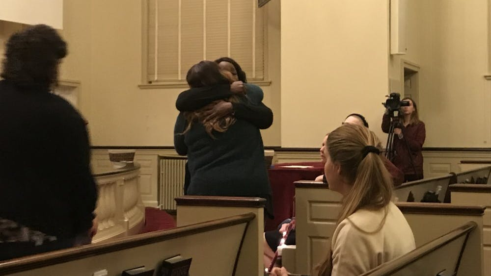 Survivors Lisa, who declined to give her last name, and Tay Washington embrace each other after sharing their stories with attendees at the First United Methodist Church Friday.