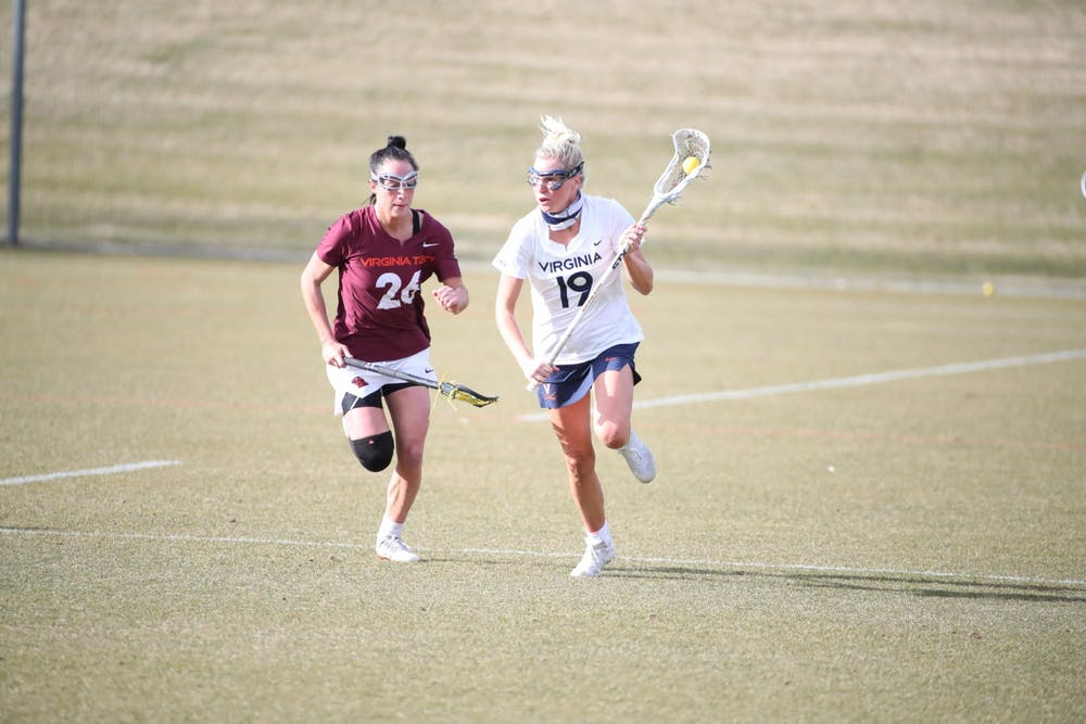 <p>Virginia junior midfielder Annie Dyson runs past Virginia Tech senior midfielder Paige Petty in the rivalry's first matchup back in February.</p>