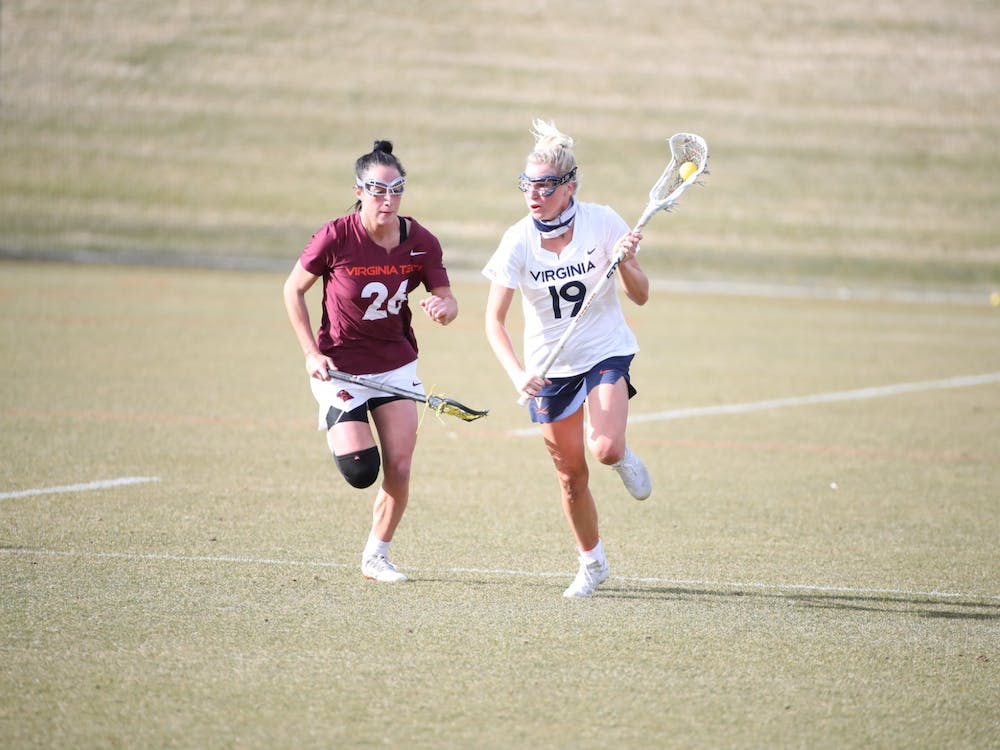 Virginia junior midfielder Annie Dyson runs past Virginia Tech senior midfielder Paige Petty in the rivalry's first matchup back in February.