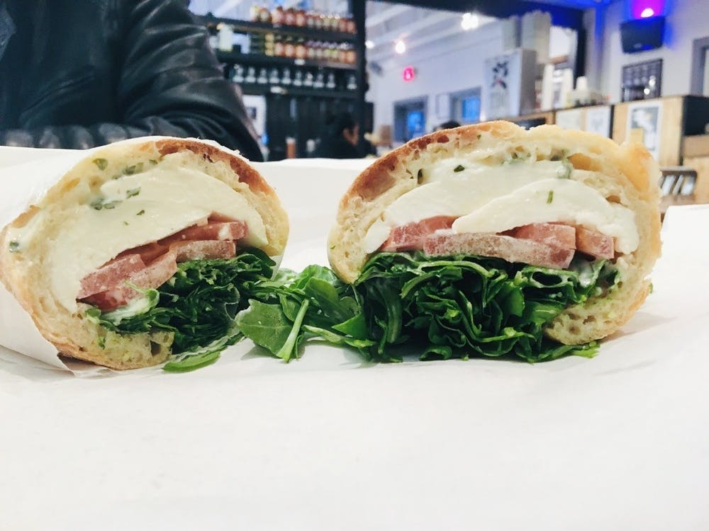 """I ordered the K.I.S.S. sandwich and I was thoroughly impressed. The ingredients were simple but worked well together — fresh mozzarella, tomato, arugula and basil mayo served on a baguette."""